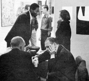 Robert Berg's photograph <i>Jack Spicer and guests at the opening of the Six Gallery, San Francisco, Halloween 1954</i>. The poet Jack Spicer is shown in the right foreground