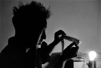 Frank looking at negatives in California while photographing <i>The Americans</i> (1956)