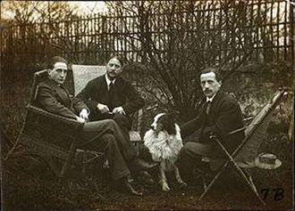 This 1914 photograph shows the Duchamp brothers, (from left to right) Marcel Duchamp, Jacques Villon, and Raymond Duchamp-Villon with Jacques Villon's dog Pipe in the garden of Jacques' Puteaux studio.